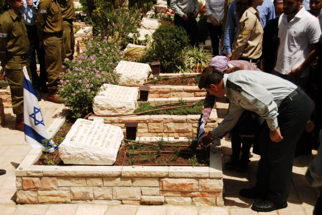 Lt. Gen. Gabi Ashkenazi lays a flag down on the late Maj. Eliraz Peretz's grave