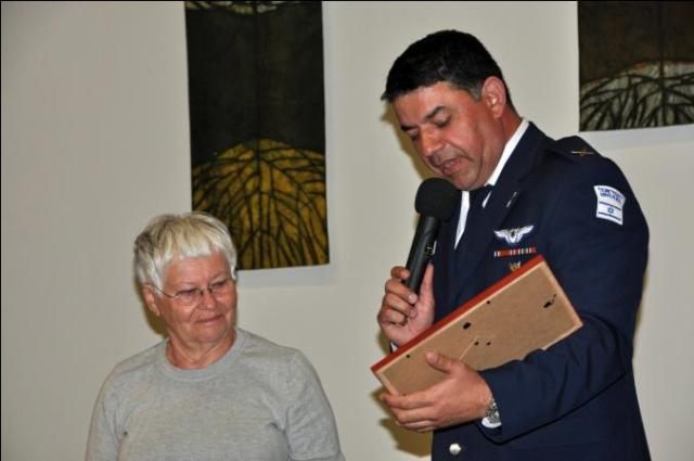 Aliza Landau, a Holocaust survivor is presented with a gift by the IDF's Witness in Uniform Program