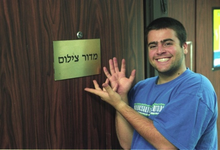 "Sgt. Lior Ziv, of blessed memory, next to the door of his office in the Spokesperson's Unit. The sign reads ""Photography Department""."