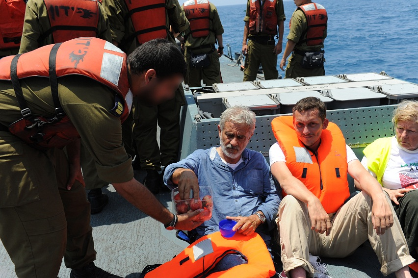 Al-Karama Passenger accepts food and water given to him by an IDF Navy soldier